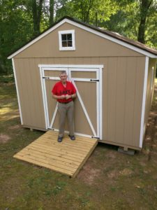 Man in front of his new gardening shed
