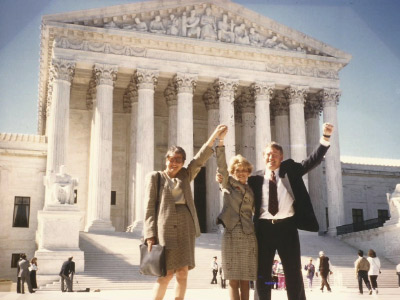 Photo of three adults standing in front of a government building